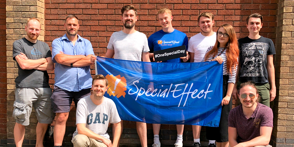 Nine staff members around SpecialEffect flag