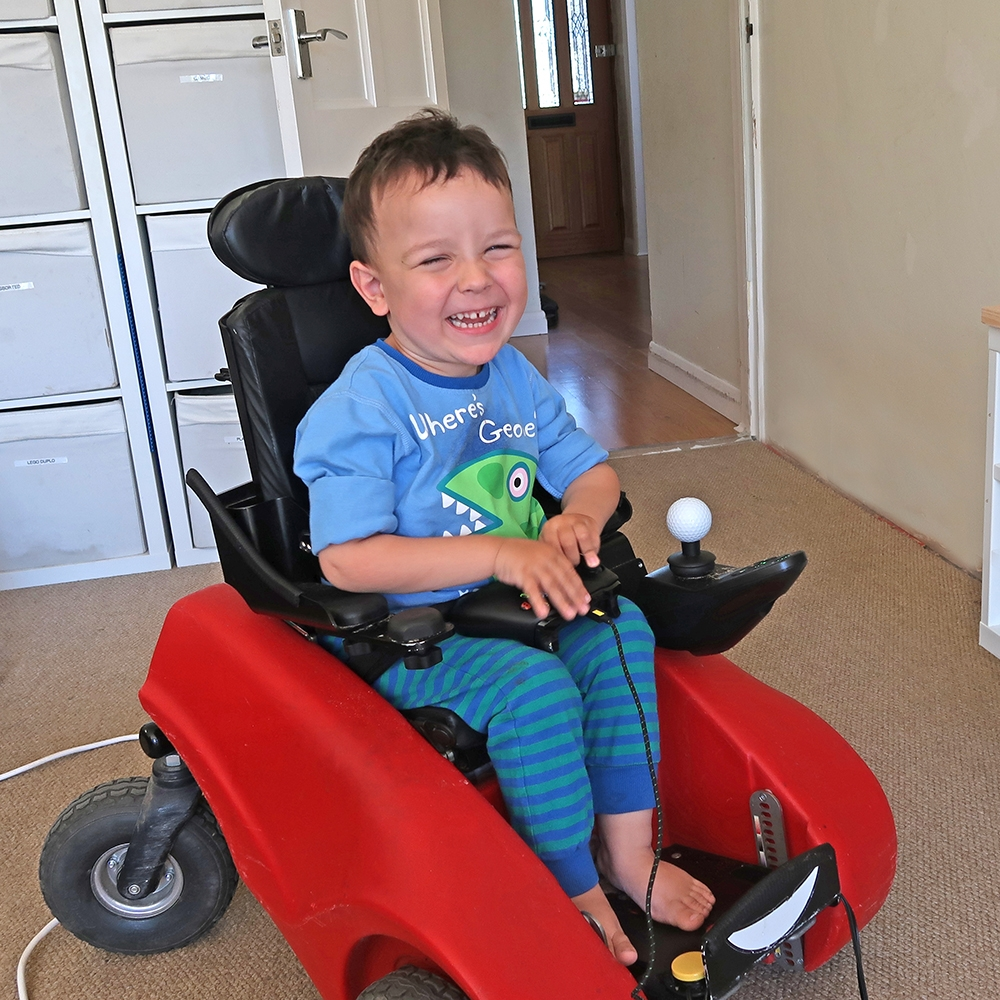 A smiling Oliver sitting in his buggy with his new gaming control setup
