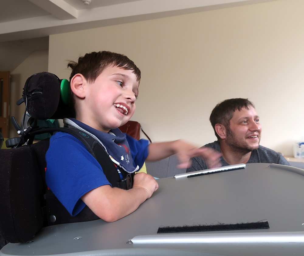 Jake playing a game sitting next to his smiling father