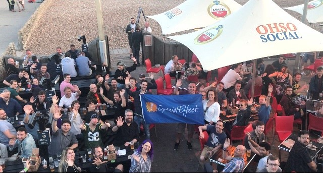 Crowd of people holding SpecialEffect flag