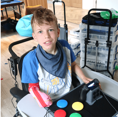 Young boy in wheelchair looking directly at the camera