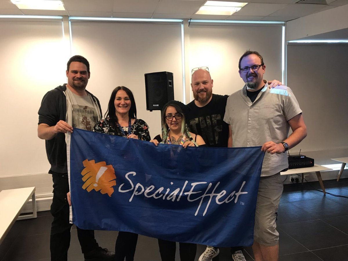 Team of Sony employees holding a SpecialEffect flag