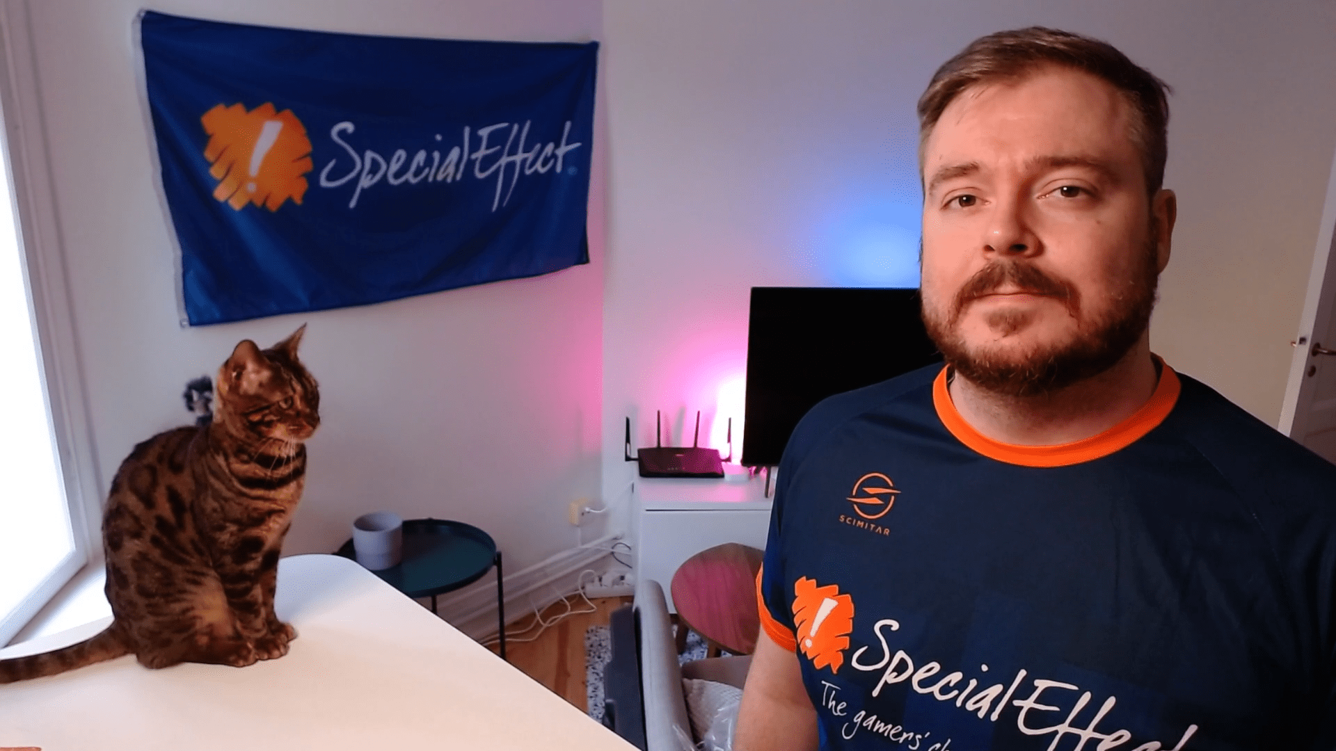 Young bearded man in a SpecialEffect tee-shirt and a tabby cat