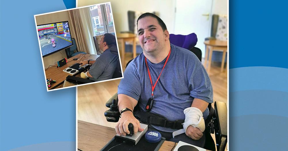 Smiling man in wheelchair playing video game